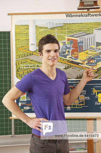 Teenager-Junge zeigt auf die Karte  lächelnd  Portrait