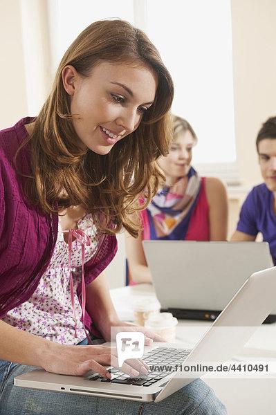 Teenage Girl mit Laptop und Schülern im Hintergrund