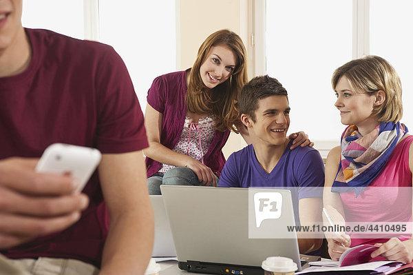 Studenten  die einen Laptop mit einem Mann benutzen  der das Handy im Vordergrund hält.
