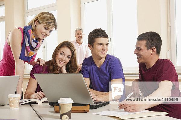 Deutschland  Emmering  Schüler diskutieren und nutzen Laptop mit Lehrer im Hintergrund