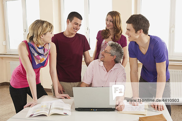 Germany  Emmering  Teacher and students using laptop