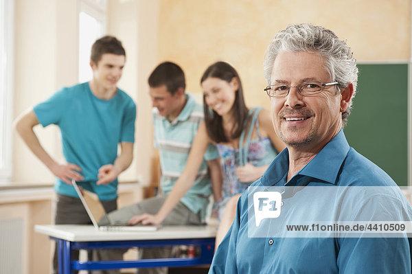 Senior Mann lächelt mit Studenten mit Laptop im Hintergrund