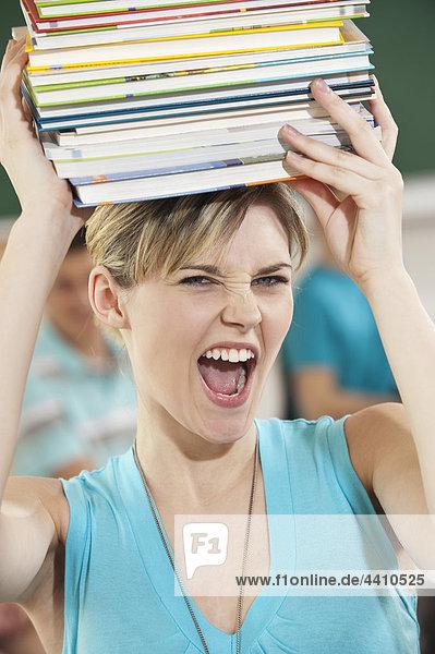 Junge Frau trägt einen Stapel Bücher mit Studenten im Hintergrund.