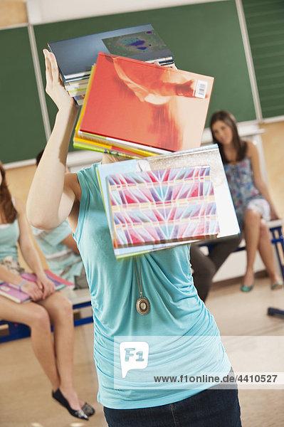 Teenagermädchen mit fallenden Büchern vom Kopf