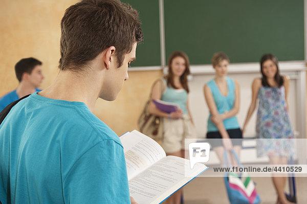 Teenage Boy Lesebuch mit Schülern im Hintergrund