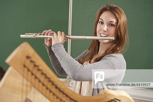 Teenager Mädchen bläst Flöte  lächelnd  Portrait