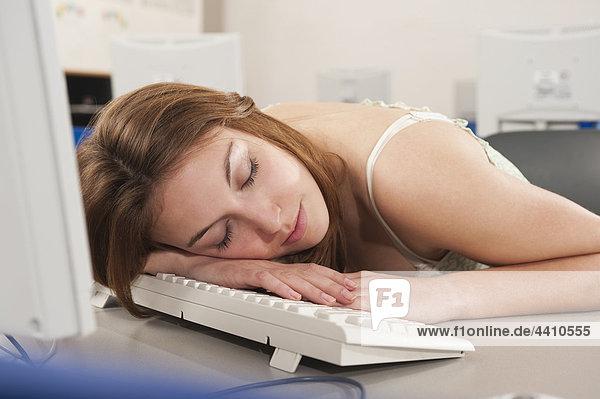 Teenager-Mädchen schläft im Computer-Labor.