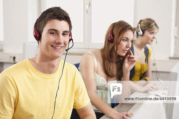 Teenager-Junge lächelt mit Schülern  die den Computer im Hintergrund benutzen.