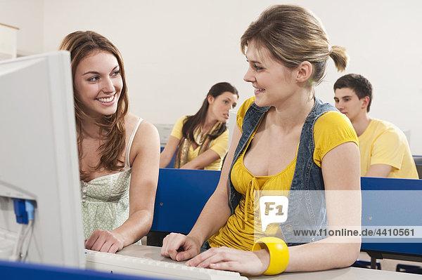 Teenager Mädchen und Frau lächelnd mit Schülern im Hintergrund