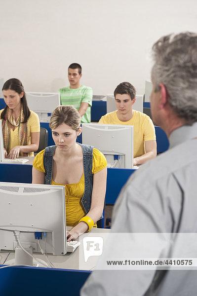 Deutschland  Emmering  Dozent beobachten  Studenten mit Computer im Computerlabor