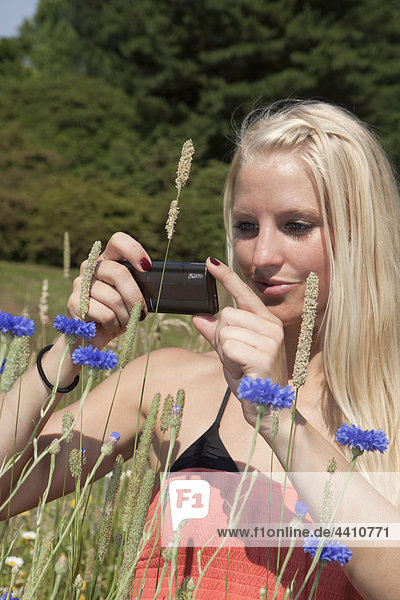 Young woman capturing an image with cell phone