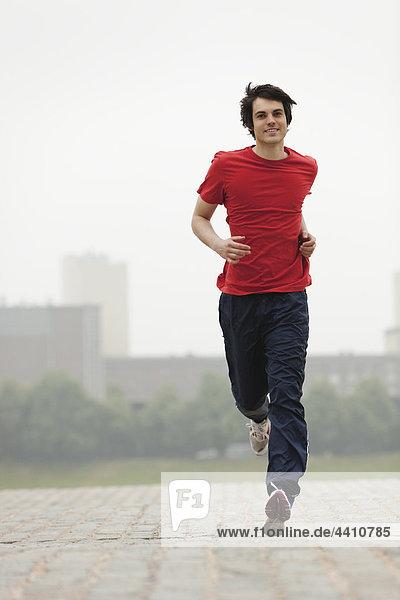 Junger Mann joggt  lächelt.
