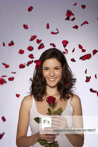 Junge Frau mit roter Rose  lächelnd  Portrait