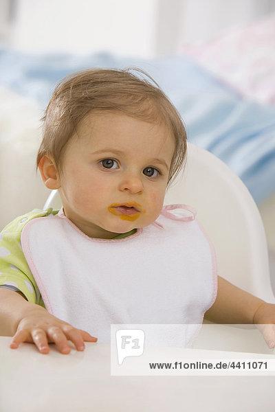 Mädchen (6-11 Monate) auf Hochstuhl sitzend  Portrait