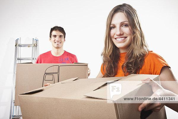 Junges Paar mit Pappkartons  lächelnd  Portrait