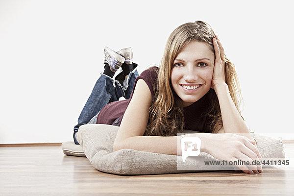Junge Frau auf dem Boden liegend  lächelnd  Porträt