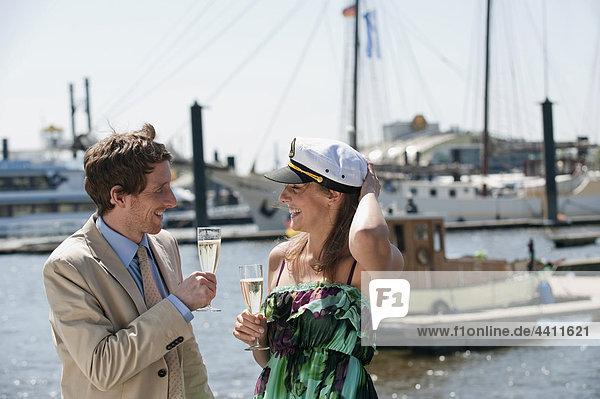 Deutschland  Hamburg  Paar trinkt Champagner  lächelnd