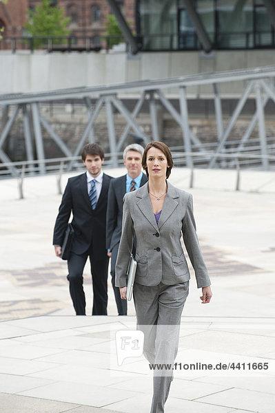 Geschäftsfrau  die mit Geschäftsleuten im Hintergrund geht.