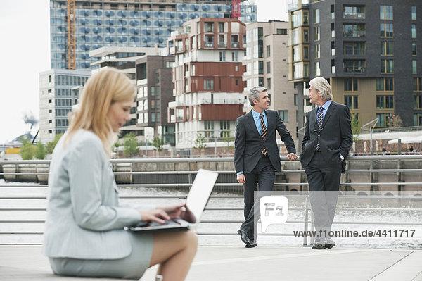 Geschäftsfrau mit Laptop und Geschäftsmann im Hintergrund