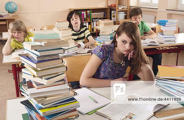 Mädchen mit Kopf in den Händen mit Schülern im Hintergrund