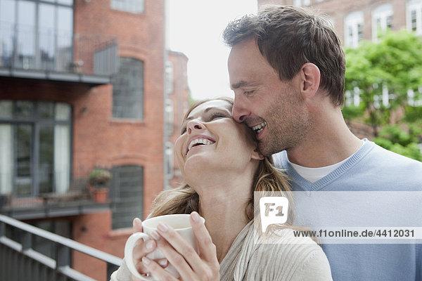 Deutschland  Paar genießt auf dem Balkon mit Frau mit Kaffeetasse