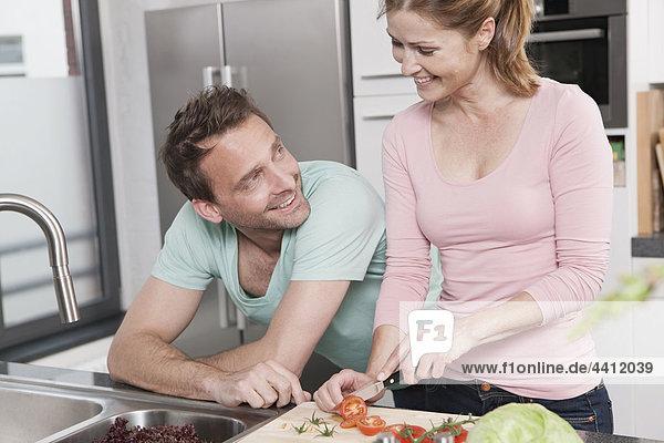 Deutschland  Paar Zubereitung Salat in der Küche  lächelnd