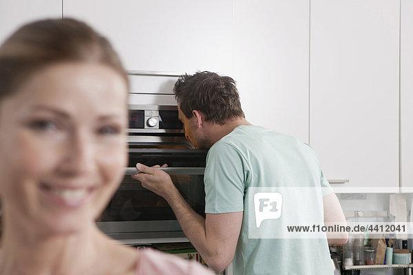 Deutschland  Mann schaut in den Ofen mit lächelnder Frau im Vordergrund