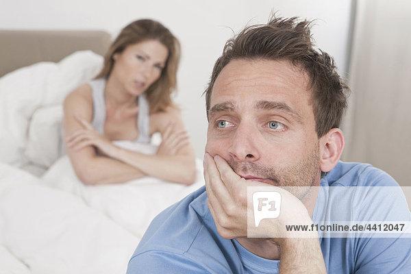 Deutschland  Mann denkt mit Frau im Hintergrund