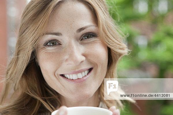 Deutschland  Frau hält Kaffeetasse  Porträt  lächelnd