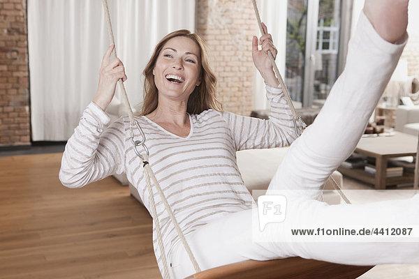 Deutschland  Frau auf Schaukel sitzend und genießend