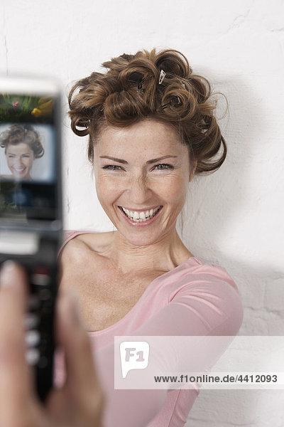 Deutschland  Frau fotografiert sich mit Handy  lächelnd