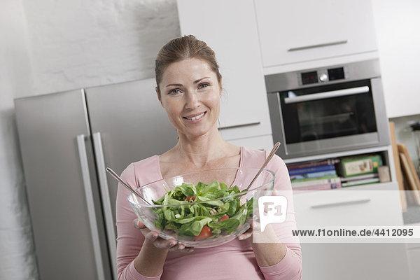 Deutschland  Frau stehend mit Salatschüssel  Portrait  lächelnd