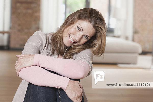 Deutschland  Porträt einer Frau mit umarmenden Knien und Lächeln