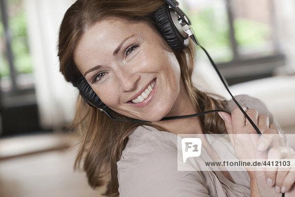 Deutschland  Nahaufnahme einer Frau beim Musikhören  Portrait
