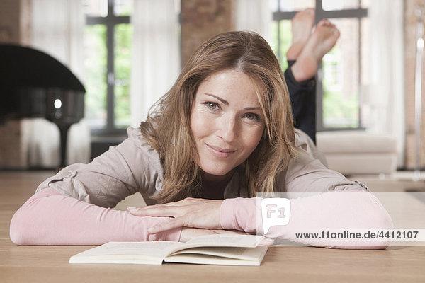 Deutschland  Frau liegt und liest Buch  lächelnd  Porträt