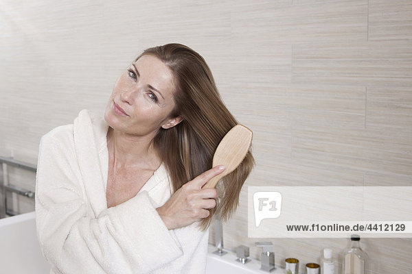 Deutschland  Frau im Bad kämmt sich die Haare  Portrait