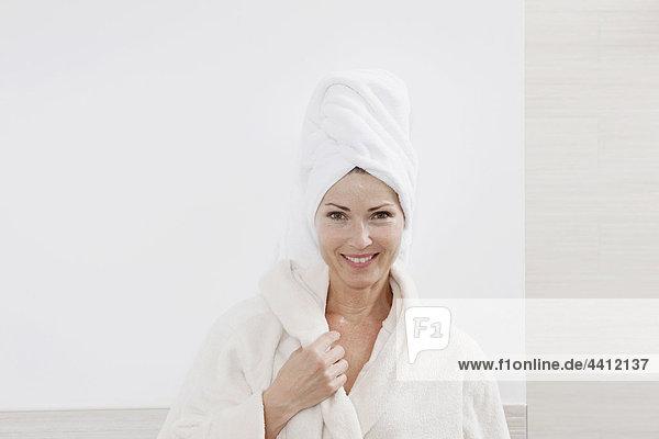 Deutschland  Frau mit Bademantel im Bad  lächelnd  Portrait