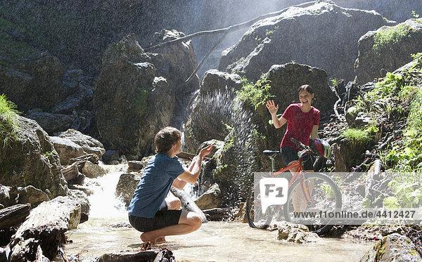 Österreich  Salzkammergut  Mondsee  Junges Paar mit Fahrrad und Wasserfall im Hintergrund