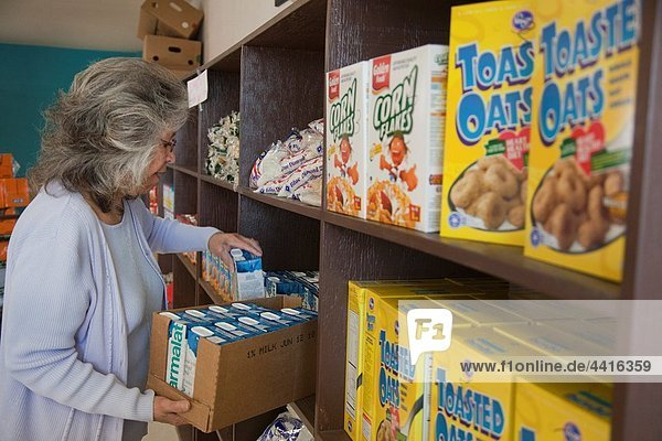 Alamosa  Colorado - A worker stacks food on shelves at a food bank operated by La Puente La Puente is a nonprofit agency providing social services in Colorado´s San Luis Valley  where much of the population lives below the poverty level