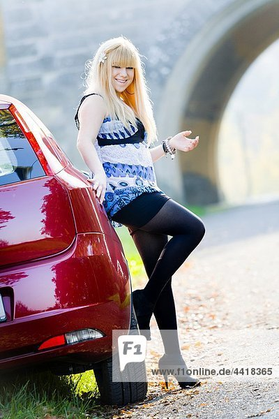 Waiting next to a Red car happy young woman