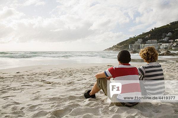 Two boys sitting on beach