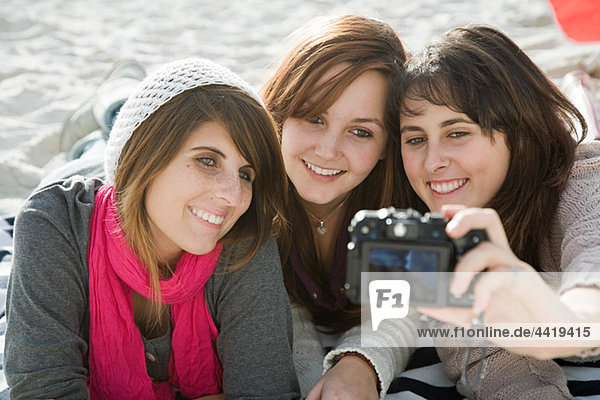 Female friends taking photograph of themselves