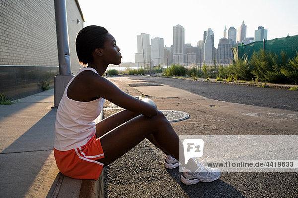 Läufer auf dem Bürgersteig sitzend
