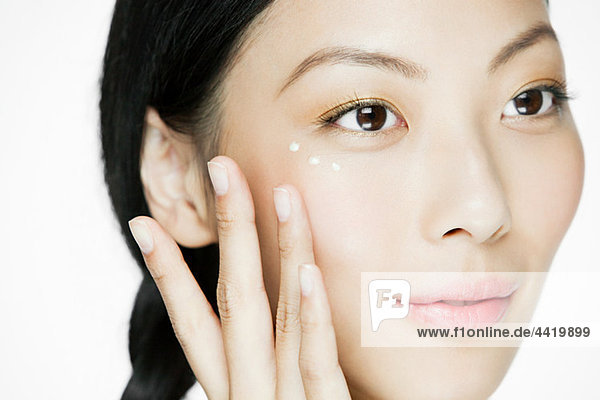 Junge Frau mit Augencreme