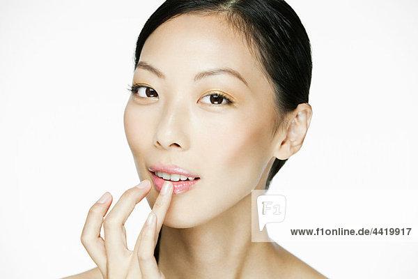 Junge Frau beim Auftragen von Lipgloss