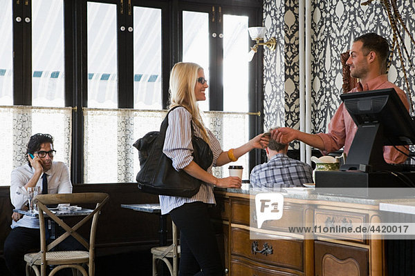 Frau bezahlt den Kaffee
