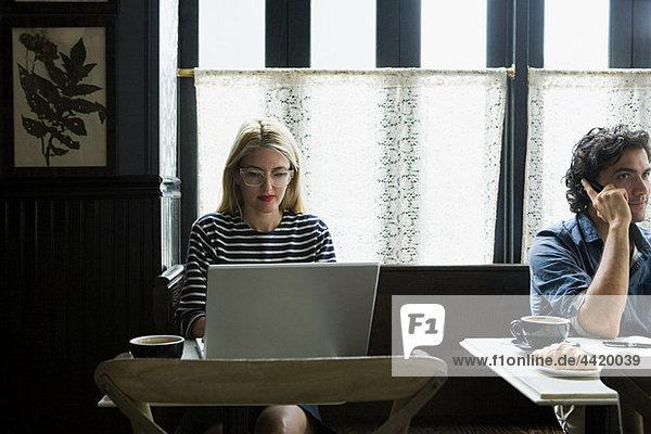 Frau arbeitet am Laptop im Coffee Shop