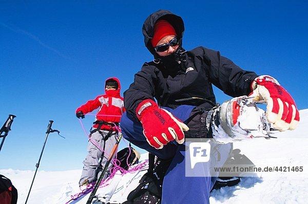 Frau des Scoopens Schnee unter Skischuh