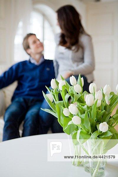Junges paar sitzen auf Sessel  Bouquet von weißen Tulpen im Vordergrund Junges paar sitzen auf Sessel, Bouquet von weißen Tulpen im Vordergrund