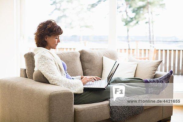 Frau sitzend auf Sofa und Surfen internet